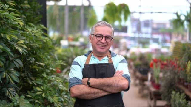 stockvideo's en b-roll-footage met portret van tuin markt medewerker / eigenaar - armen over elkaar