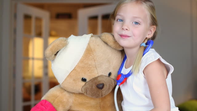 ms portrait of girl (4-5) dressed as doctor sitting by teddy bear with bandage on head / brussels, brabant, belgium - bandage stock videos & royalty-free footage