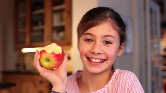 CU Portrait of girl (8-9) eating apple / Brussels, Brabant, Belgium