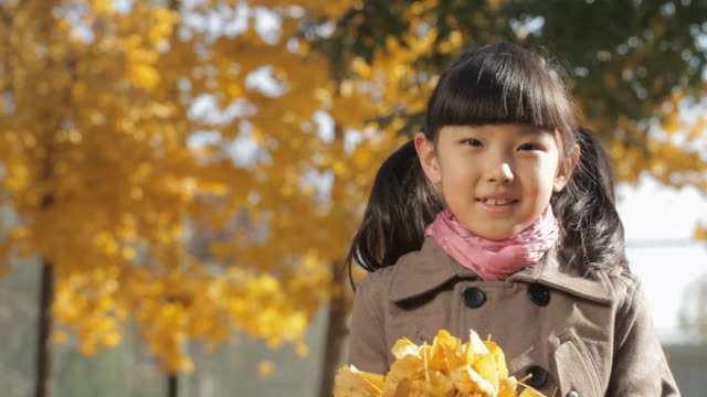cu portrait of girl holding dry leaves and smiling at camera in park / china - オーバーコート点の映像素材/bロール
