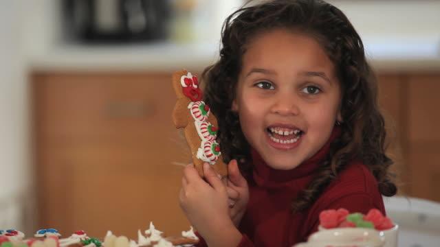 cu portrait of girl (4-5) holding gingerbread men cookie/ richmond, virginia, usa - 4歳から5歳点の映像素材/bロール