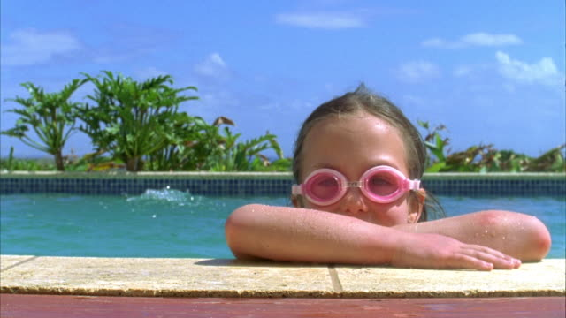 CU, Portrait of girl (6-7) leaning on poolside, Vieques, Puerto Rico