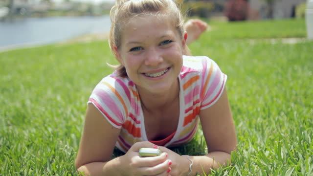 ws portrait of girl (14-15) lying on grass / cape coral, florida, usa - endast en tonårsflicka bildbanksvideor och videomaterial från bakom kulisserna