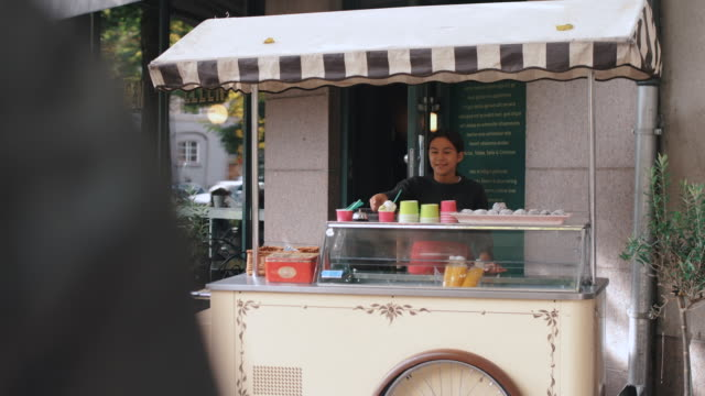 portrait of girl selling ice cream at stand in city - awning stock videos & royalty-free footage