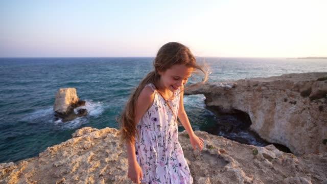 vidéos et rushes de verticale de fille restant et riant sur la falaise sur le bord de mer à chypre - falaise
