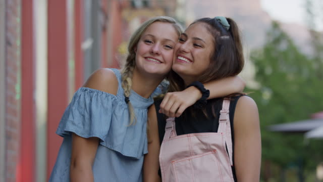 portrait of girl surprised when friend kisses her cheek / provo, utah, united states - nur weibliche teenager stock-videos und b-roll-filmmaterial