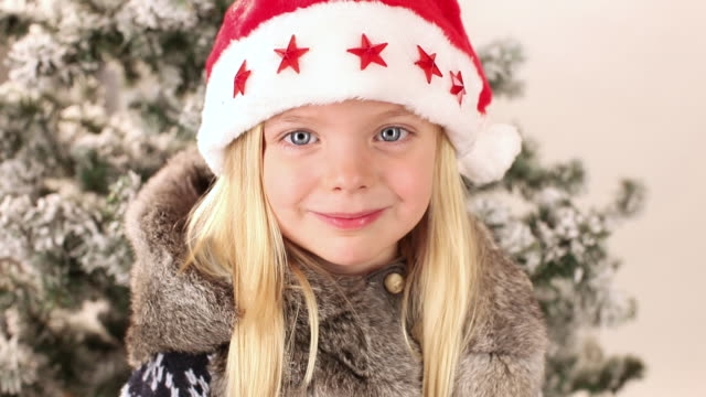 cu portrait of girl (4-5) wearing santa hat, holding christmas decorations in front of eyes and sticking out tongue in studio - santa hat stock videos and b-roll footage