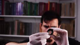 Portrait of goldsmith who examines gold ring through magnifier glass and surprisingly raises brows