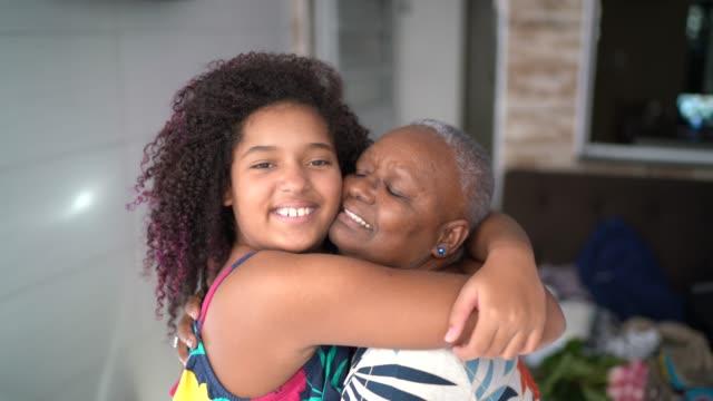 vídeos de stock, filmes e b-roll de retrato da neta e da avó em casa - abraçar