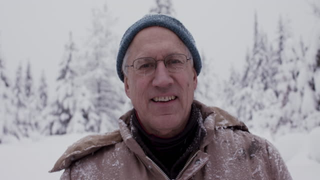 portrait of grandfather looking at camera smiling after cutting christmas tree in the snow in usa. - grandmother stock videos & royalty-free footage