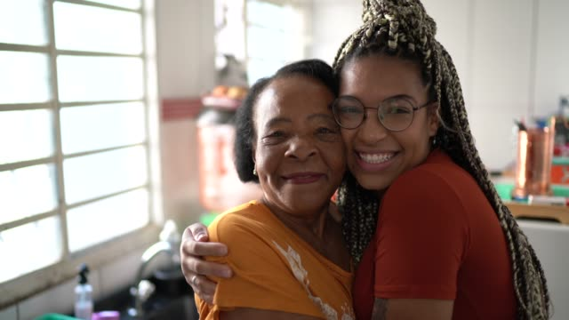 portrait of grandmother and granddaughter embracing at home - granddaughter stock videos & royalty-free footage
