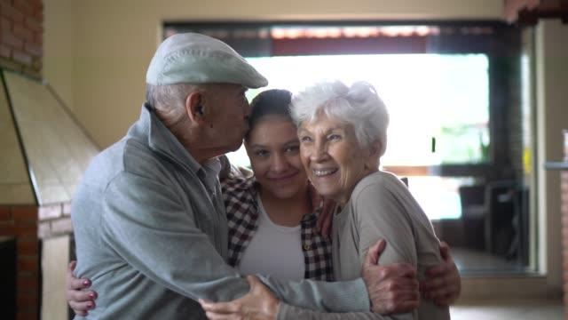 vidéos et rushes de verticale des grands-parents avec la petite-fille d'adolescent à la maison - affectueux