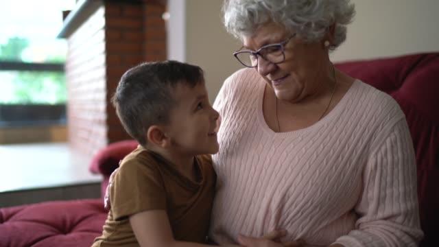 vidéos et rushes de verticale du petit-fils sur les genoux de grand-mère à la maison - petit enfant