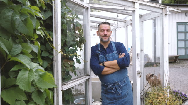 Portrait of greenhouse male owner smiling while leaning at doorway
