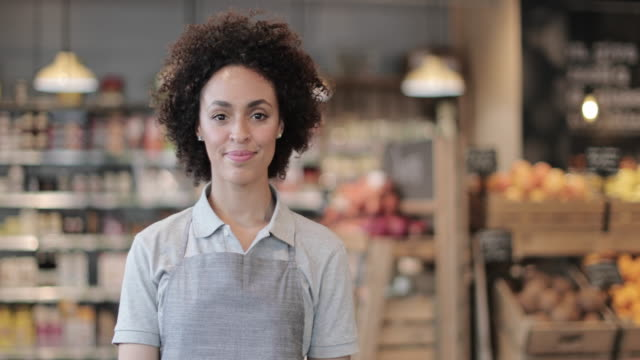 vidéos et rushes de portrait of grocery sales assistant looking to camera - employment issues
