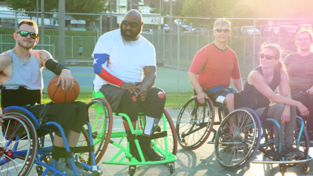 pan portrait of group of adaptive athletes on outdoor basketball court after practice on summer evening - wheelchair basketball stock videos and b-roll footage
