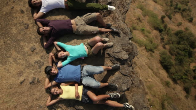 vídeos y material grabado en eventos de stock de portrait of group of friends relaxing on a cliff of mountain - manos detrás de la cabeza