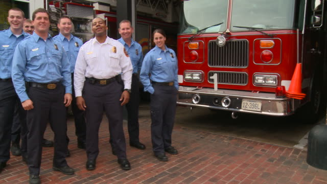 WS PAN Portrait of group of smiling fire fighters in uniform in front of fire station/  Richmond, Virginia
