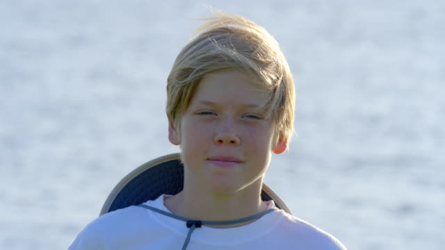 portrait of handsom blond boy 12 years old looking at the camera. positive emotions. summer. sun light. lake on background. - telephoto lens stock videos and b-roll footage