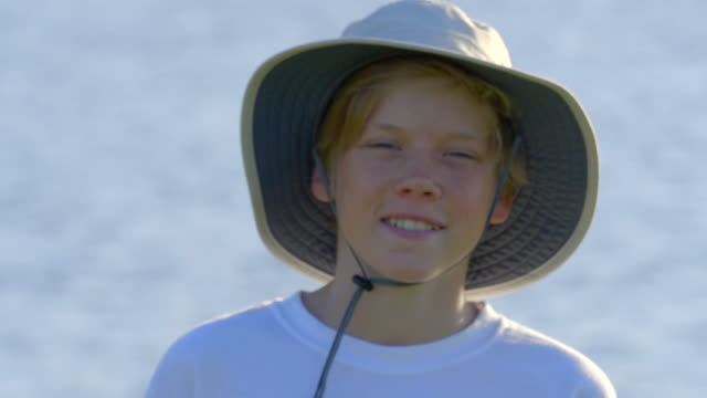 portrait of handsom boy 12 years old in the hat. looking at the camera. positive emotions. summer. sun light. lake on background. - telephoto lens stock videos and b-roll footage