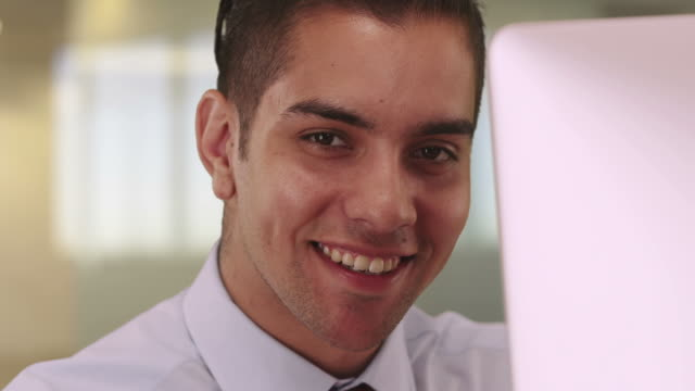 portrait of handsome latino business man sitting at computer smiling - neckwear stock videos and b-roll footage