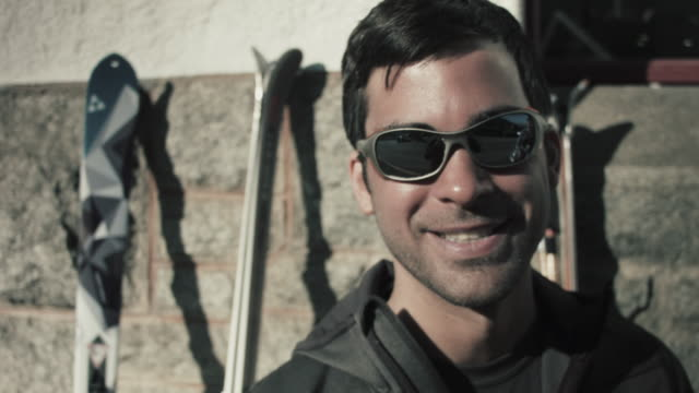 vídeos de stock e filmes b-roll de portrait of handsome skier with sunglasses smiling into camera at hut with skies in the background - casaco de esqui