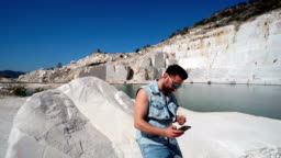Portrait of handsome stylish hippie guy in jeans clothes and sun glasses making selfie using a smartphone and drinking beer, marble lake pamukkale