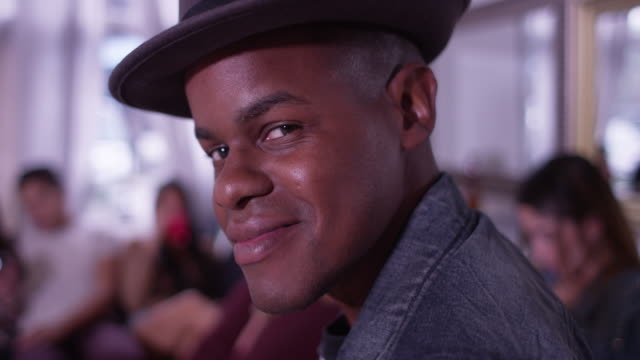 portrait of handsome young black hipster man smiling and laughing with group of friends partying in background - プエルトリコ人点の映像素材/bロール