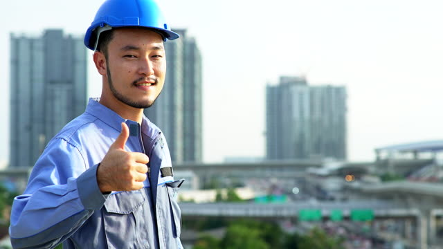 Portrait of happiness smile Asian engineering at the top of the construction site.