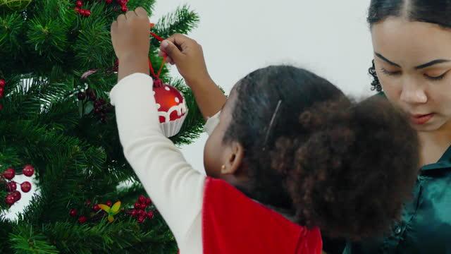 vídeos de stock, filmes e b-roll de retrato da felicidade para menina etnia africana idade 3 anoolde wering roupas vermelhas preparar e decorar árvore x'mas com a família. conceito de espírito natalino. - três pessoas
