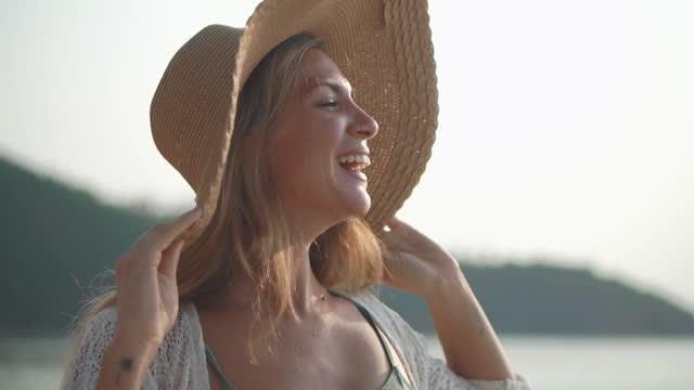 vídeos de stock, filmes e b-roll de retrato da felicidade jovem mulher da etnia latino-americana e hispânica aos 27 anos de idade vestida de vestido branco enquanto ela está tocando seu chapéu de capô com a vista e o vento na praia. férias - conceito istock. - beach holiday