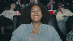 Portrait of happy African American teenager laughing watching film in cinema