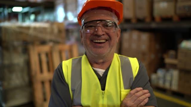 vídeos de stock e filmes b-roll de portrait of happy and smiling worker at warehouse - trabalhador de armazém
