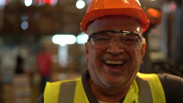 porträt eines glücklichen und lächelnden arbeiters im lager - qualitätsprüfer stock-videos und b-roll-filmmaterial