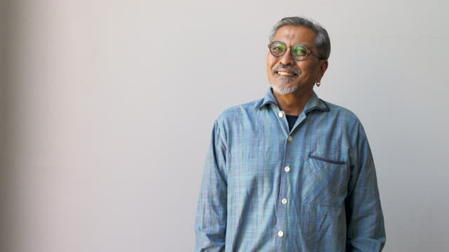 portrait of happy asian senior man wearing glasses and looking at camera isolated on grey background - malaysian ethnicity stock videos & royalty-free footage