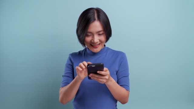 portrait of happy asian woman using a smartphone isolated on blue background. 4k video - standing stock videos & royalty-free footage