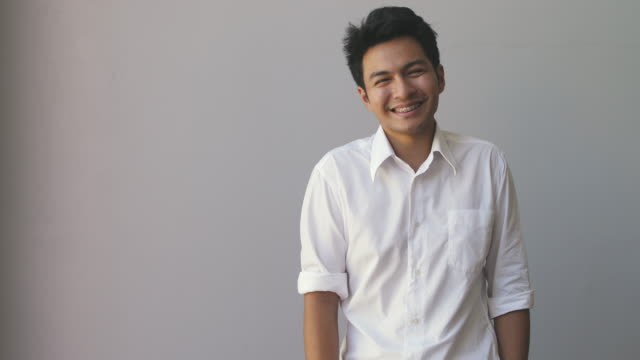 portrait of happy asian young man wearing a white shirt looking at camera isolated on grey background - malaysian ethnicity stock videos & royalty-free footage
