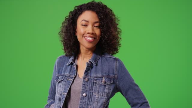 vídeos y material grabado en eventos de stock de portrait of happy black woman in jean jacket posing playfully on green screen - casual clothing