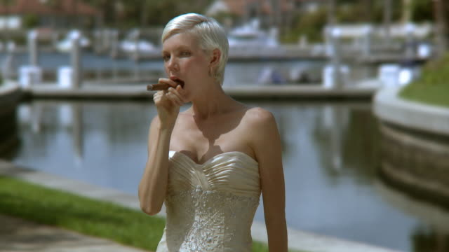 stockvideo's en b-roll-footage met ms portrait of happy bride with cigar by pond, jacksonville, florida, usa - bovenlichaam