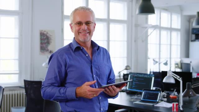 vídeos de stock e filmes b-roll de portrait of happy businessman in office - 50 anos