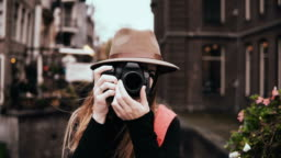 Portrait of happy Caucasian woman with a camera. Attractive cheerful lady in stylish hat taking a picture 4K front view