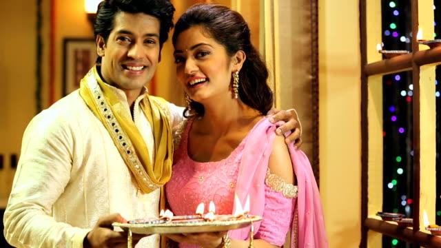 vídeos y material grabado en eventos de stock de ms pan portrait of happy couple holding diya during diwali festival at home - bandeja para servir