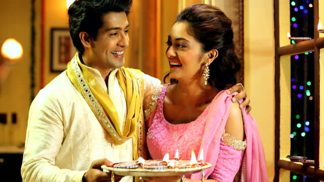 ms pan portrait of happy couple holding diya during diwali festival at home - 盆点の映像素材/bロール