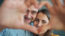 Portrait of happy couple showing heart shape with hands smiling looking at camera