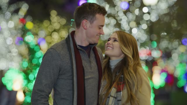 portrait of happy couple smiling at camera outdoors near christmas trees / provo, utah, united states - heterosexual couple stock videos & royalty-free footage