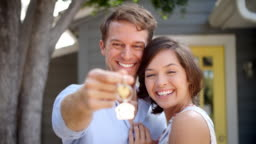 Portrait Of Happy Couple Standing Outside New Home With Keys