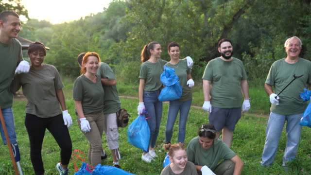 portrait of happy environmental volunteers after cleaning public park - matching outfits stock videos & royalty-free footage