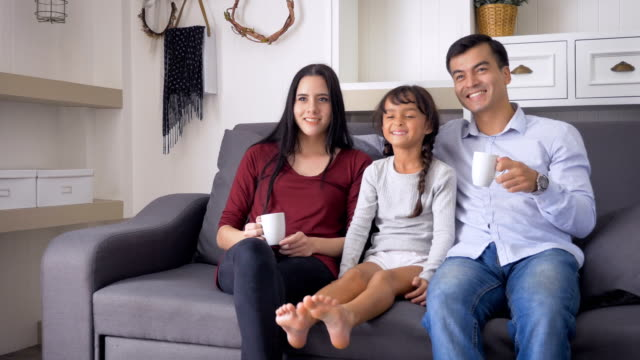 stockvideo's en b-roll-footage met portret van gelukkige familie ontspannen en thuis tv-kijken in de woonkamer - zappen