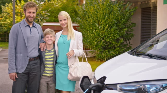slo mo portrait of happy family standing by electric car - mid adult stock videos & royalty-free footage