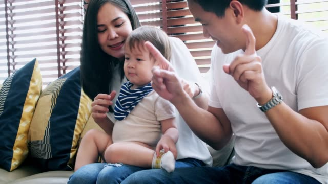 portrait of happy family waving hands at home. military father, mother and baby saying hello. - baby waving stock videos & royalty-free footage